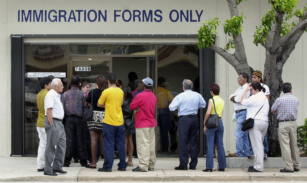FILE: A line forms near the entrance of the Immigration and Naturalization Service office in Miami, on April 30, 2001.