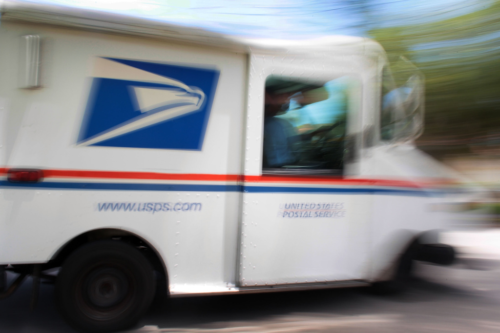 File: U.S. Postal Service mail carrier, Alberto Jo, drives the mail truck as he delivers mail to homes on Aug. 5, 2010 in Miami, Florida.