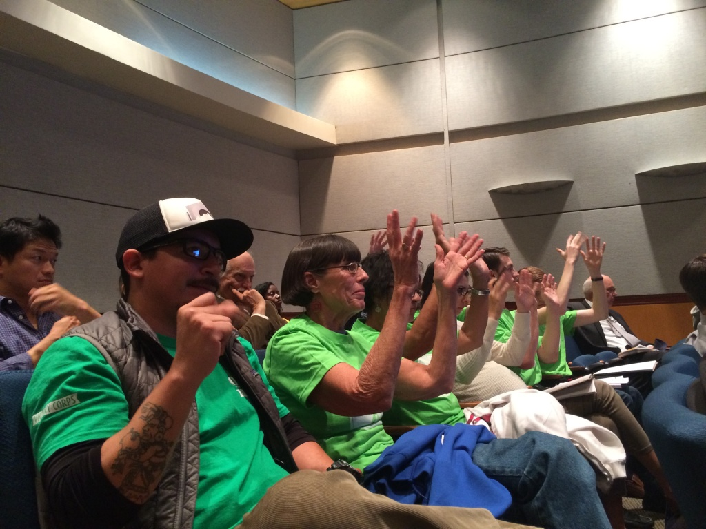 Roberto Morales, Cindy Koch and other members of the Sierra Club raise hands in support of calls for stricter rules on nitric-oxide emissions at a governing board meeting of the South Coast Air Quality Management District on Dec. 4, 2015.