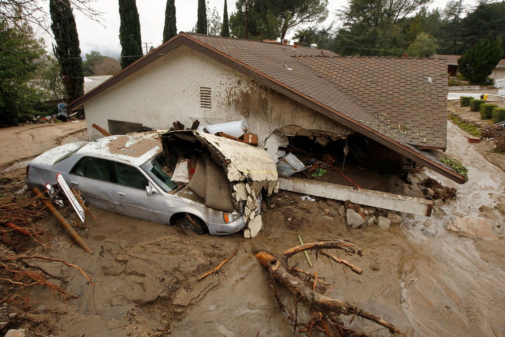 In this file photo, a debris flow damages a home after heavy rains caused mudslides February 6, 2010 in La Canada Flintridge, California. The National Weather Service is warning residents living near recent burn areas, including parts of Glendora, that a pair of heavy rain storms expected this week could cause mud flows and flooding.