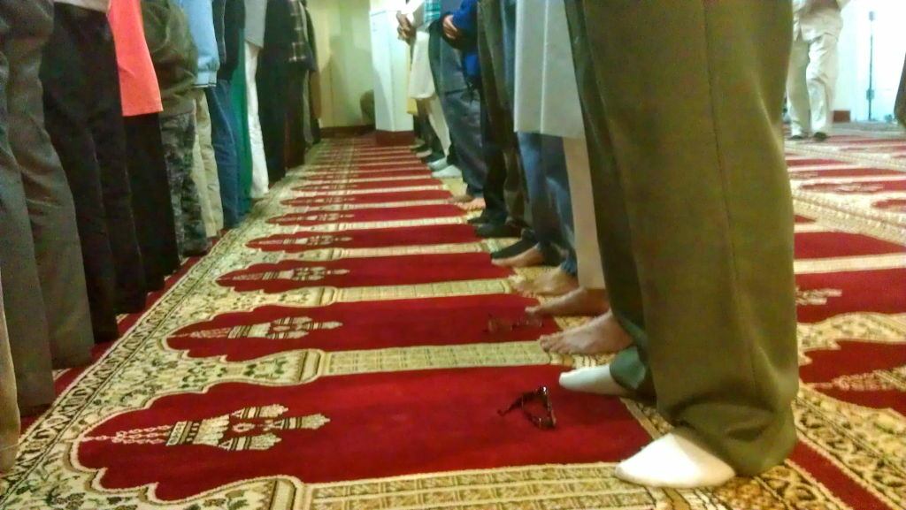 Male worshipers at a mosque stand at prayer.