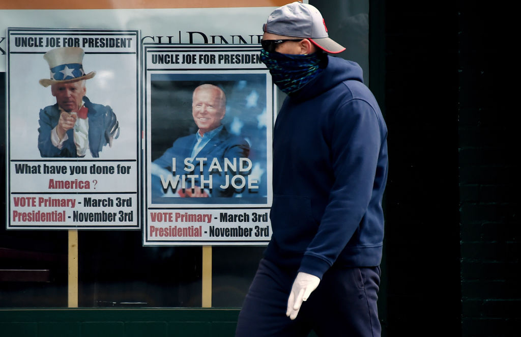 A man wearing a face mask walks past signs for Joe Biden's 2020 presidential campaign amid the coronavirus outbreak on May 11, 2020 in Alexandria, Virginia.