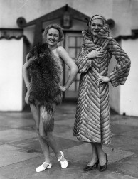C. 1930: A fashion show including bathing suits, clothes for children, furs, and wedding dresses was held in a large Spanish-style courtyard. View 12: Young women standing next to each other model two distinctly different furs. The model on the right wears a long gray striped coat, tan hat, and black heels; the woman on the left appears to be bare underneath an animal pelt, possibly a fox fur pelt, which is draped over her right shoulder and around her hips, and wearing white shoes.