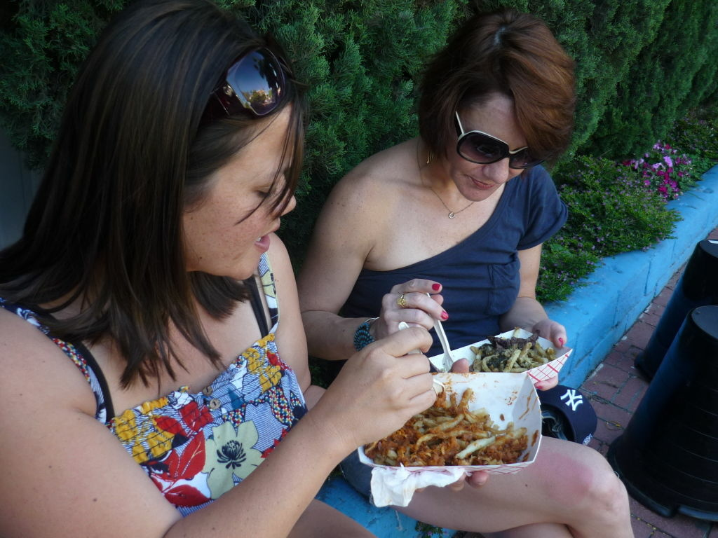 Carey McDonald and Suzanne Stackle pull up some brick fence at Blue Collar in Echo Park and dive into gourmet french fries from the Frysmith Food Truck.