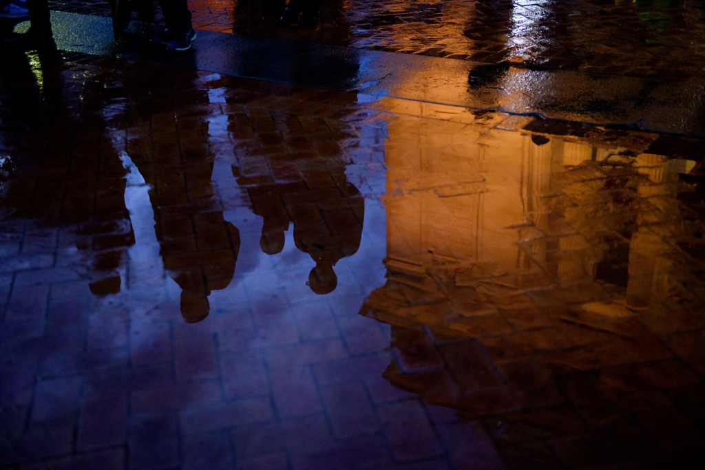 People are reflected in a puddle after attending a service at the Soldiers and Sailors Memorial Hall to honor and mourn the victims of Saturday's mass shooting at the Tree Of Life Synagogue on October 28, 2018 in Pittsburgh, Pennsylvania.