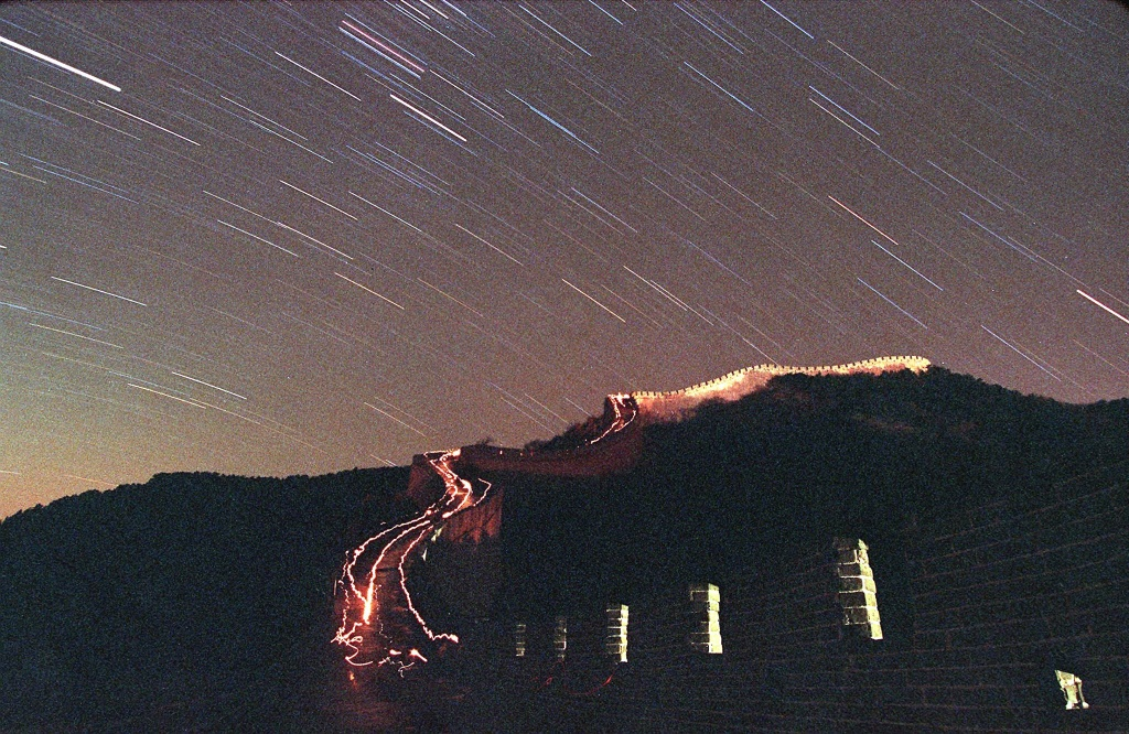 The Leonid meteor shower lights up the sky above China's Great Wall as stargazers brave the -4 degrees temperature and walk up the wall with their flashlights 18 November in Badaling.