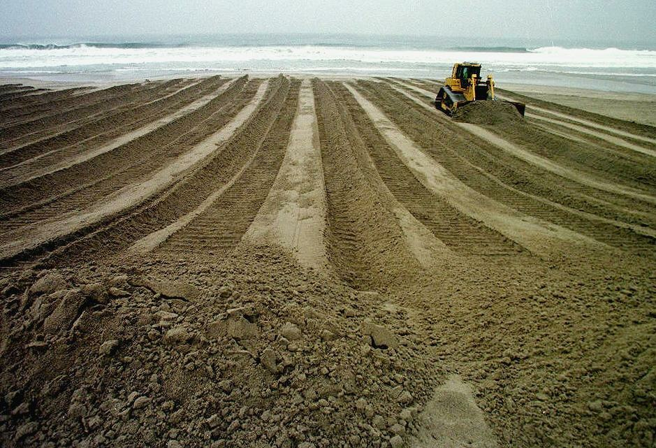 December 5, 1997: A bulldozer creates a pattern in the sand as it works to reinforce a 15-foot sand berm along Venice Beach as the first El Nino-related storm hits the west coast of the United States. Sand berms all along the coast of Los Angeles have been strengthen to prevent storm surges due to elevated sea levels created by the El Nino.