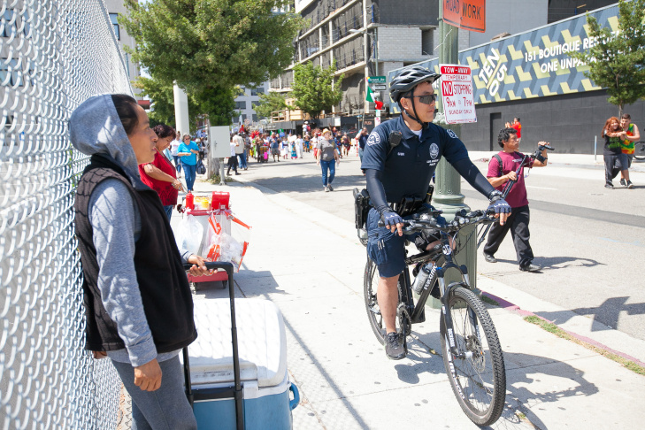 Police patrolled the peaceful march on bikes and stood by on side streets on foot and in squad cars. Vendors selling cold drinks and hot dogs followed the march at the May Day rally in downtown Los Angeles on May 1, 2016.