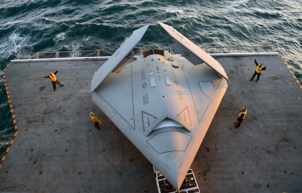 Sailors move an X-47B Unmanned Combat Air System (UCAS) demonstrator onto an aircraft elevator aboard the aircraft carrier USS George H.W. Bush (CVN 77) May 14, 2013 in the Atlantic Ocean. George H.W. Bush is scheduled to be the first aircraft carrier to catapult-launch an unmanned aircraft from its flight deck. The Navy plans to have unmanned aircraft on each of its carriers to be used for surveillance and be armed and used in combat roles.