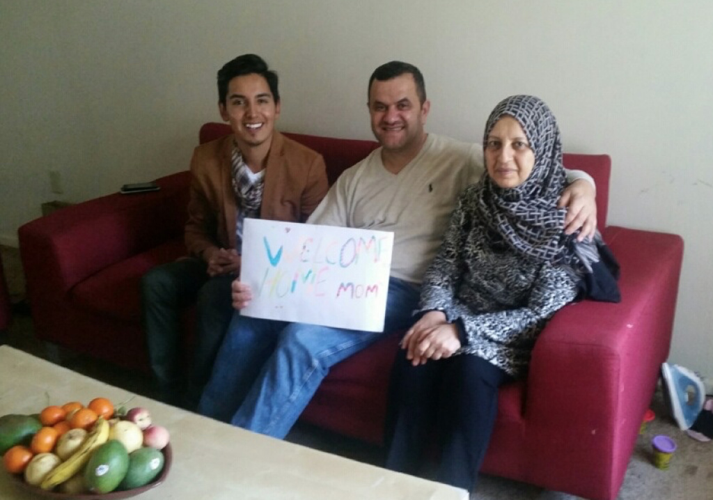 Jose Serrano of World Relief, a refugee resettlement agency, sits with Isam Zabiba, center, and Mayasah Witwit, right, the day after her arrival from Iraq.