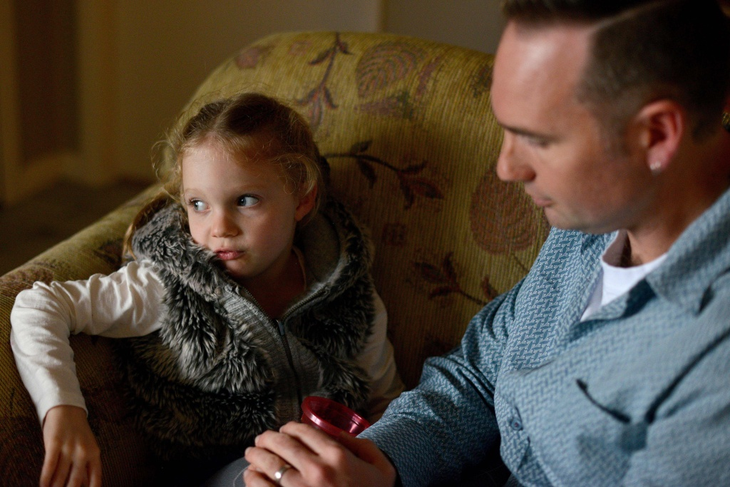 This photo taken on June 16, 2017 shows four-year-old Arielle Harding sitting on the sofa with her father Tim as he holds a container of medical marijuana at their home in Newcastle, 160km north of Sydney.
