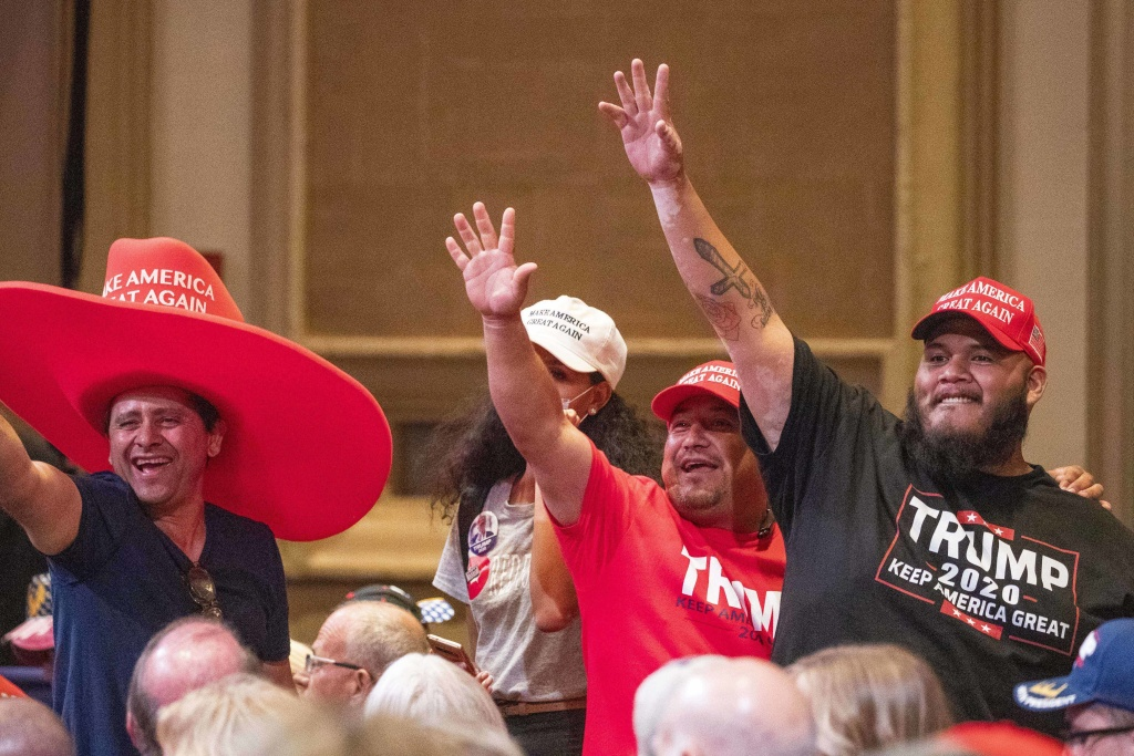 Supporters of President Trump wave during a Latinos for Trump Roundtable at the Arizona Grand Resort in Phoenix on Sept. 14.
