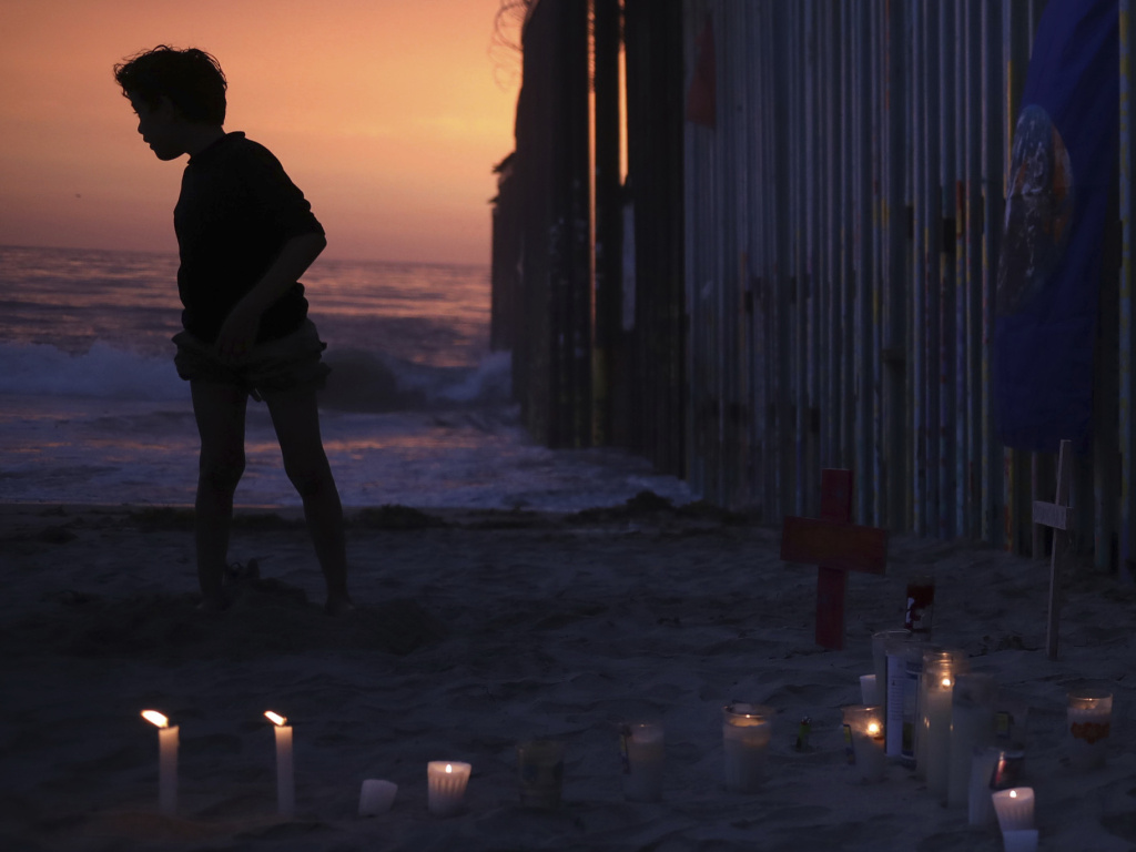 A youth stands by the border fence that separates Mexico from the U.S. Sunday, where candles and crosses stand in memory of the father and daughter who died during their journey toward the U.S.