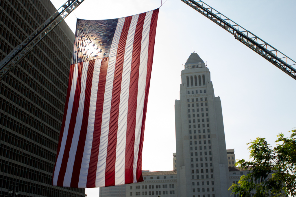 File: An American flag is suspended in the air overlooking Los Angeles City Hall.