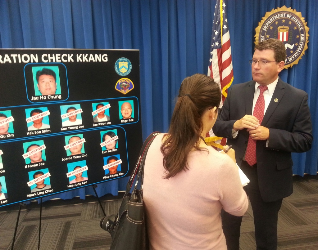 FBI special agent Timothy Delaney stands near a poster board depicting the alleged perpetrators of a fraudulent check passing ring that targeted Korean Americans.