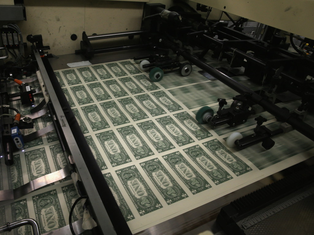 Sheets of $1 bills run through the printing press in 2015 at the U.S. Bureau of Engraving and Printing in Washington, D.C. National debt is expected to reach an all-time high of 107% of gross domestic product in 2023.