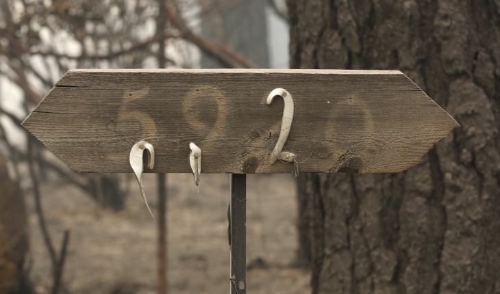 A pair of melted address numbers hang from a sign near a home destroyed by a wildfire Saturday, Sept. 12, 2015, in Mountain Ranch, Calif. The blaze exploded amid triple-digit temperatures and land parched from several years of drought. (AP Photo/Rich Pedroncelli)