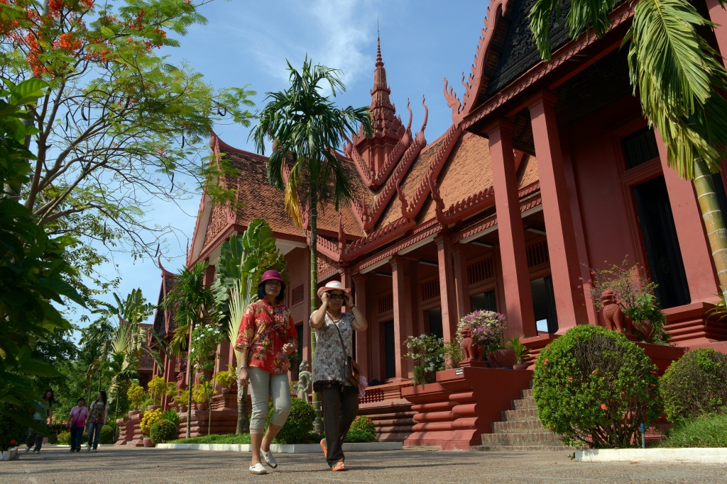Tourists walk past the National Museum building in Phnom Penh on May 10, 2013. Cambodia is expected to receive 4 million foreign visitors in 2013, an expected 12 percent rise year-on-year.