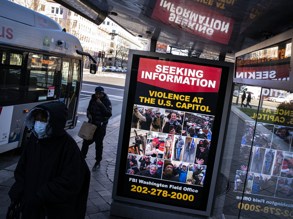 At a bus stop on Pennsylvania Avenue Northwest in Washington, D.C., a notice from the FBI seeks information about people pictured during the riot at the U.S. Capitol on Wednesday.