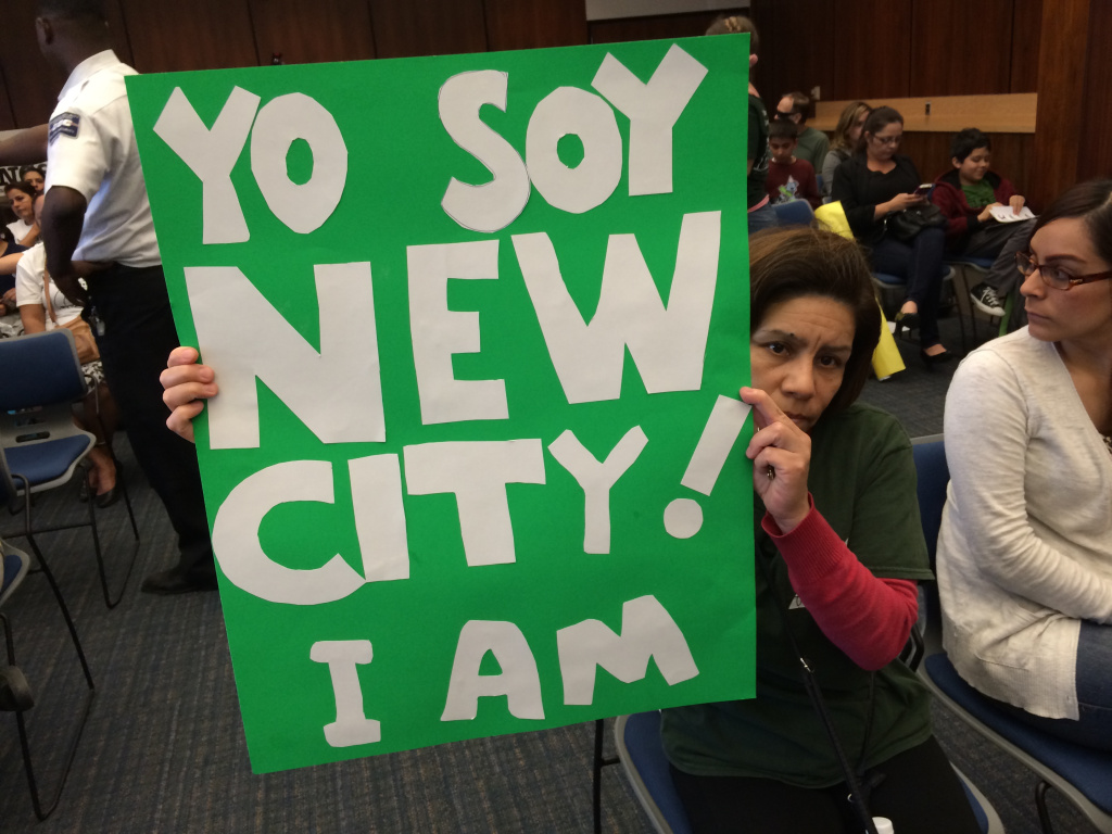 Parents and students hold signs Tuesday in favor of New City School, a bilingual charter, as the Los Angeles County Office of Education board weighs whether to allow it to stay open despite low test scores.