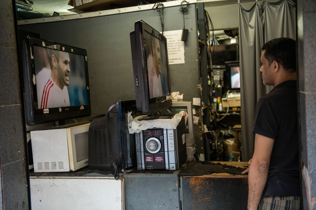 A man who works recycling home electrical appliances watches on TV the Netherlands vs Spain FIFA World Cup 2014 football match, at the Rocinha shantytown in Rio de Janeiro, Brazil, on June 13, 2014.