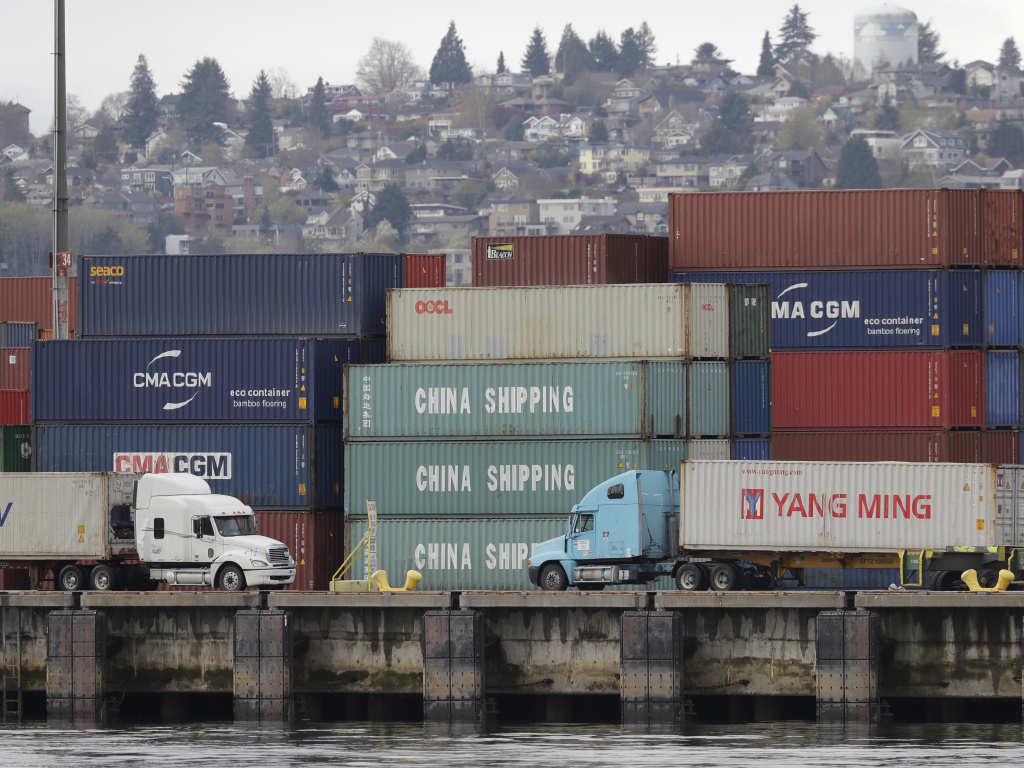 Trucks pass by cargo containers April 6 in Seattle. President Trump is preparing to impose tariffs on an additional $34 billion in Chinese imports on Friday, a move that China has promised to match.