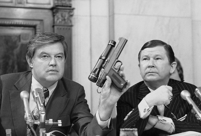 Chairman Frank Church, D- Idaho., the Senate Intelligence Committee, holds up a poison daft gun as co-chairman John G. Tower, R-Texas looks at the weapon during a session the panel's probe of the Central Intelligence Agency Tuesday, Sept. 17, 1975 in Washington.