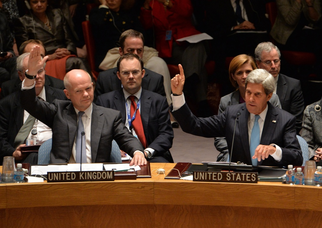 Britain's Foreign Minister William Hague (L) and US Secretary of State John Kerry (R) vote to approve a resolution that will require Syria to give up its chemical weapons during a meeting Sept. 27, 2013 at U.N. headquarters in New York.