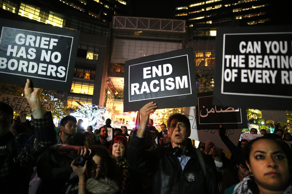 People listen to speakers at a demonstration against racism and conservative presidential candidate Donald Trump's recent remarks concerning Muslims on December 10, 2015 in New York City.