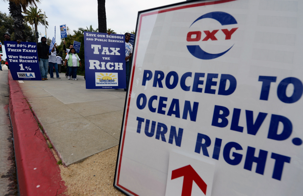 File photo: Protestors hold signs outside Fairmont Miramar hotel during Occidental Petroleum's annual shareholders meeting on May 4, 2012 in Santa Monica, California. The protestors were asking the oil company to pay billions of dollars in dodged taxes.