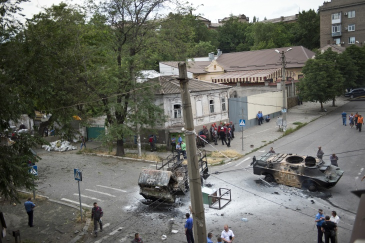 Local workers from a steel mill demolish the barricades outside the headquarters of separatist militias of the self-proclaimed 'Donetsk People's Republic' in the Ukrainian city of Mariupol on June 13, 2014. Ukrainian forces said they had hoisted the national flag over the strategic rebel-held port of Mariupol on June 13 in their biggest advance since Petro Poroshenko's election as the insurgency-wrecked country's pro-Western president.