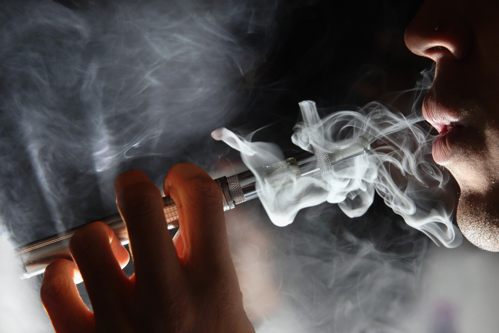 In this photo illustration, a man smokes an E-Cigarette