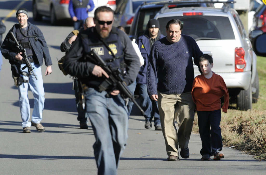 Parents leave a staging area after being reunited with their children following a shooting at the Sandy Hook Elementary School in Newtown, Conn., Friday, Dec. 14, 2012.