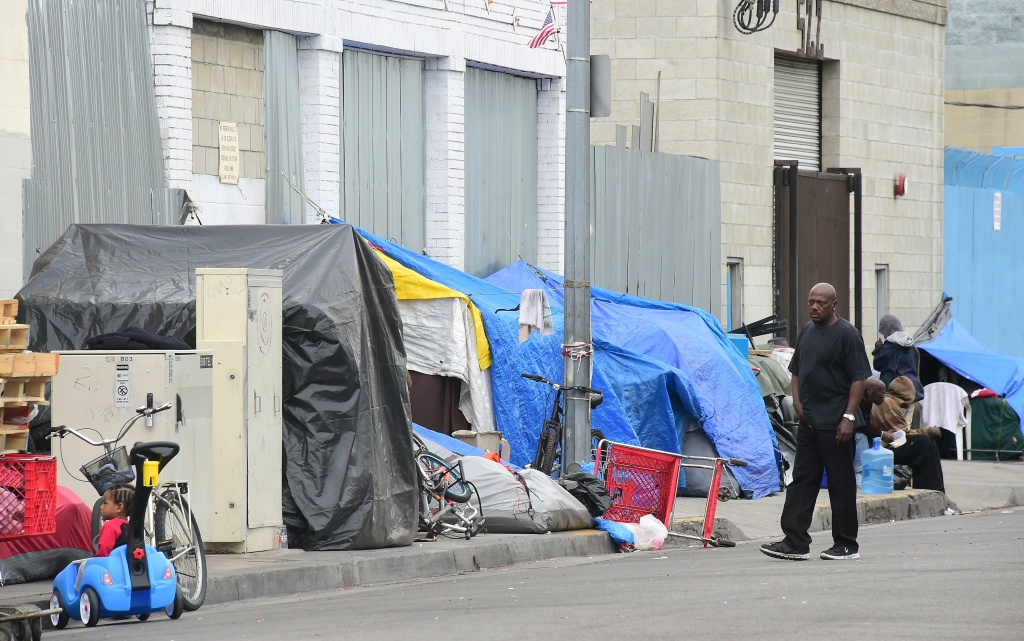 A man walks beside a row of tents for the homeless in Los Angeles.