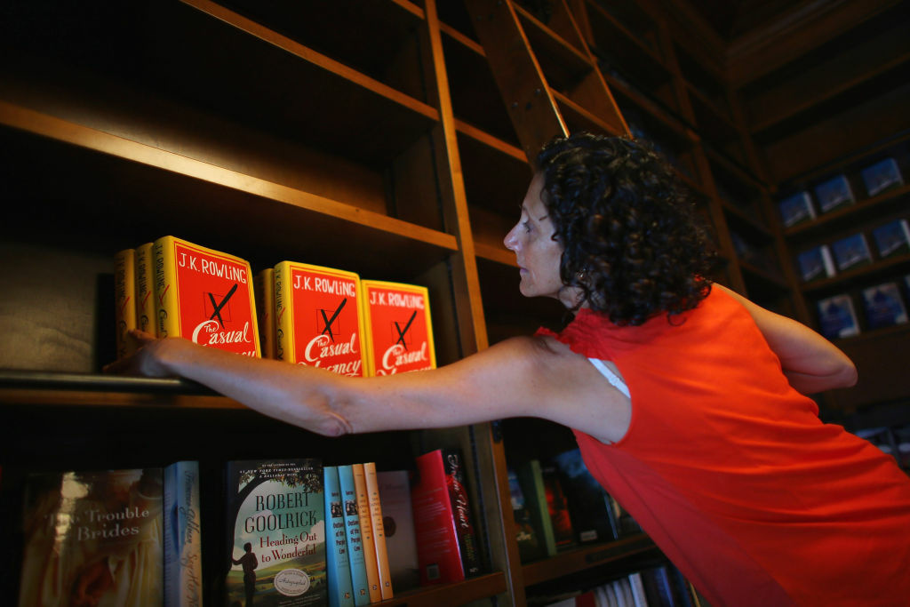 Gloria Noriega stocks the shelves with J.K. Rowling's new novel,