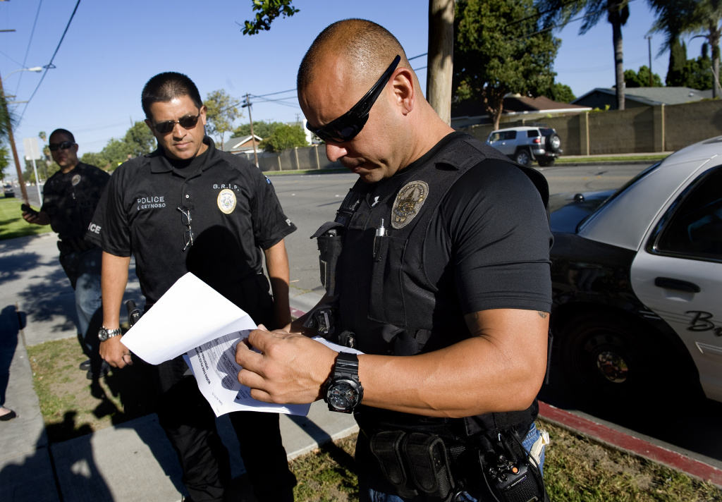 Buena Park police officer James Woo, left, Orange County District Attorney investigator Francisco Reynoso, center, and Buena Park police officer Luis Garcia look over their paperwork.