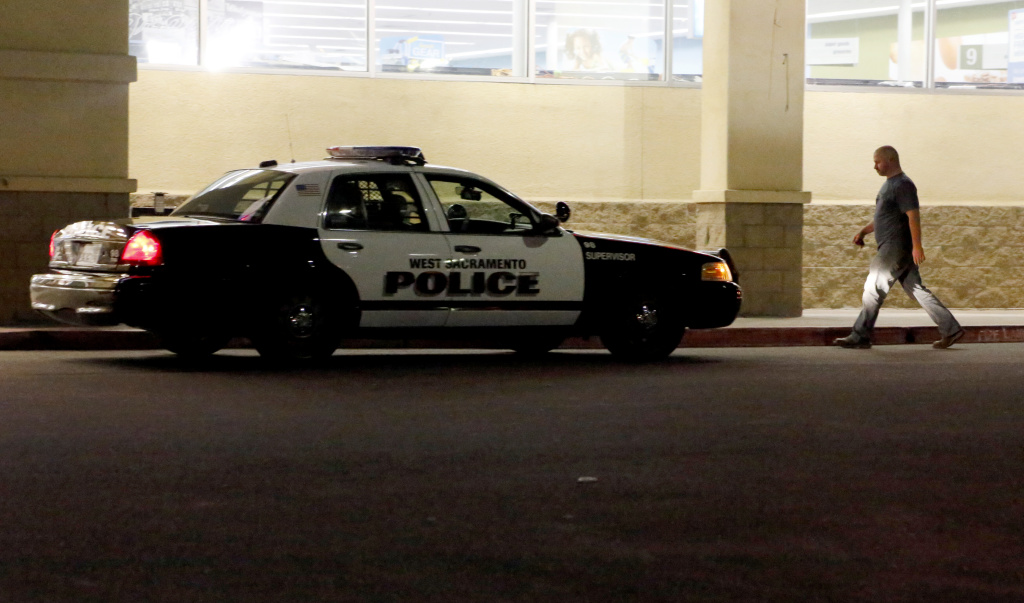 A man walks by a police patrol car on Tuesday, April 21, 2015, in a parking lot along the West Capitol Avenue strip in West Sacramento, Calif. The street is the same one where, according to court testimony, police officer Sergio Alvarez cruised for victims while on patrol. Last year, Alvarez was convicted of kidnapping and raping several of those victims, all of them addicts or prostitutes. (AP Photo/Martha Irvine)