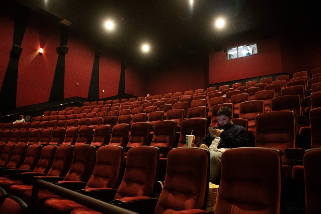 Moviegoers sit, waiting for their movie to start at the AMC Burbank theatre on reopening day in Burbank, California, March 15, 2021.