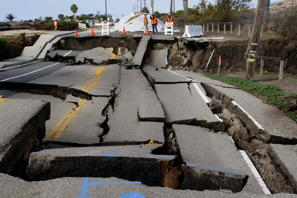 Workmen are shown at the site of a slow-moving landslide on Paseo del Mar in San Pedro.