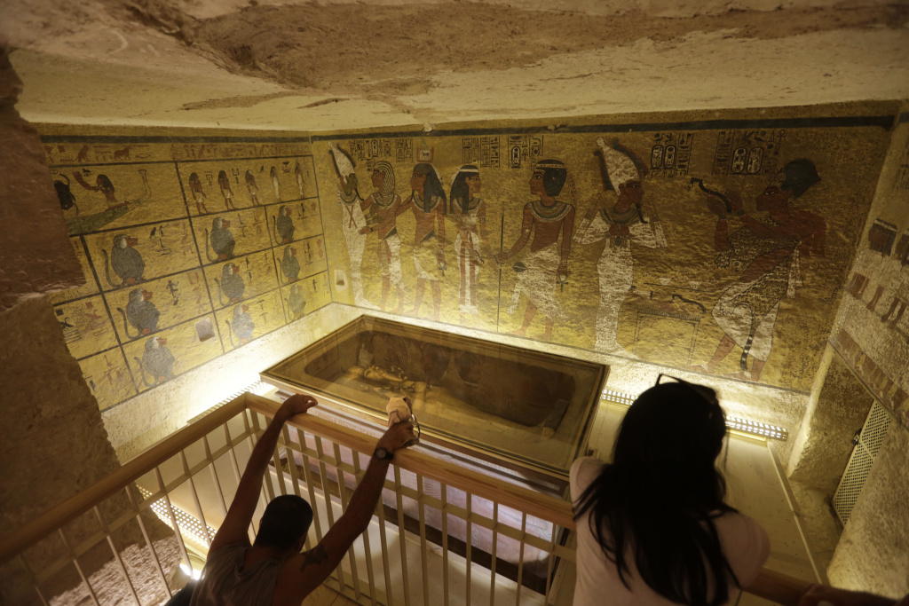 In this Thursday, Nov. 5, 2015, file photo, tourists look at the tomb of King Tut as it is displayed in a glass case at the Valley of the Kings in Luxor.