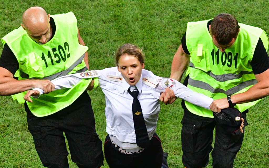 A pitch invader, a member of the Russian protest-art group Pussy Riot, is escorted by stewards during the Russia 2018 World Cup final football match between France and Croatia at the Luzhniki Stadium in Moscow on July 15, 2018.