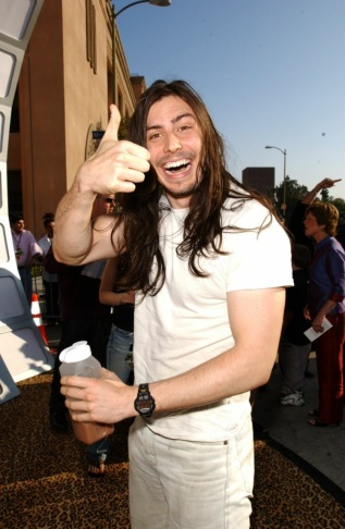 Andrew W.K. signing a fan's arm.