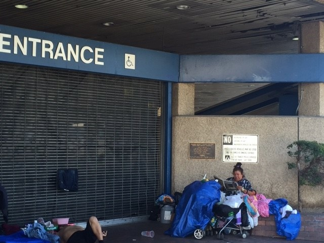 A man and woman live in a makeshift camp outside the former Greyhound bus station in Santa Ana. Homeless services providers are working to open the station as a shelter on Oct. 6.