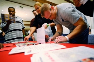 Job seeker and U.S. Navy veteran John Place (right) fills out an information form at the Los Angeles County Fire Department booth during 'Honor a Hero, Hire a Vet' job fair on Nov. 10, 2010 near LAX.