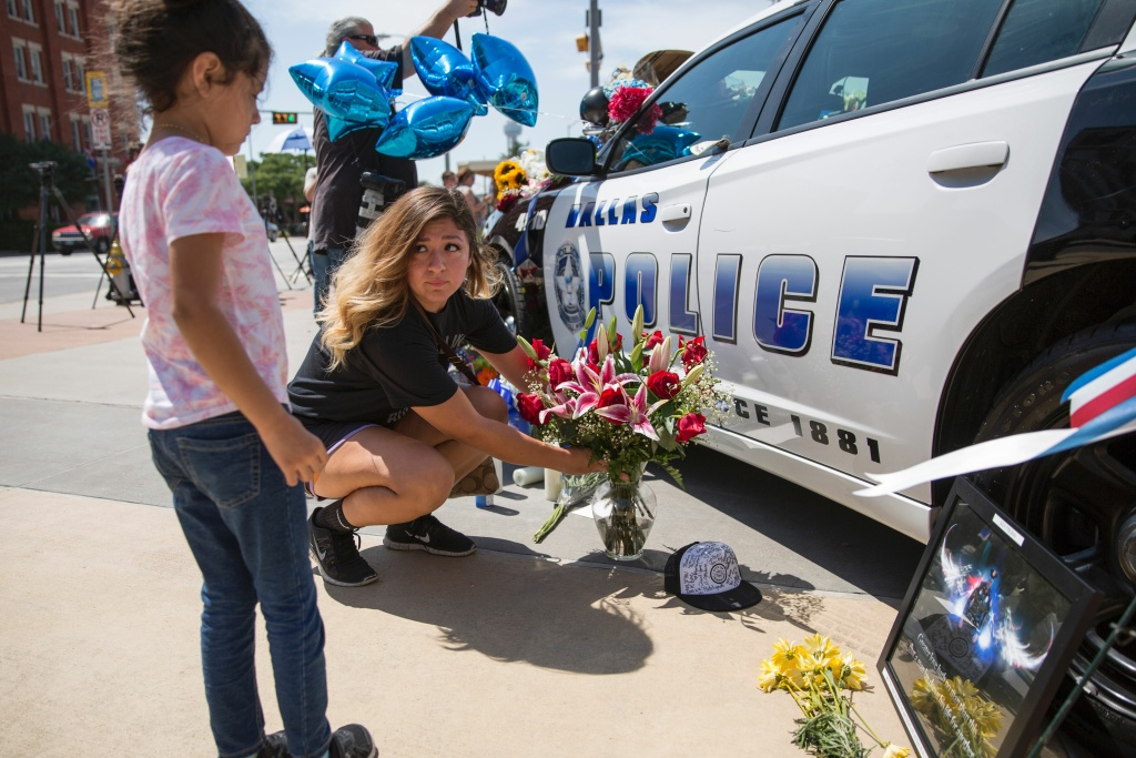 A woman and her daughter place flowers at a memorial outside the Dallas Police Headquarters on July 8, 2016, following the sniper shooting during a peaceful protest the night before.