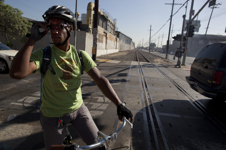 Malcolm Harris crosses the defunct train tracks along Slauson Avenue and South San Pedro Street in South Los Angeles. He commutes on a bike along this path, navigating heavy traffic and sketchy roadways. The Metropolitan Transportation Authority is considering turning the eight mile track into a green space that would offer walking and biking paths.