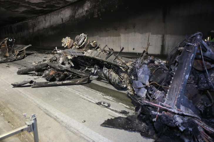 A skip loader pushes the burnt chassis of a gas tanker that crashed out of a tunnel at the I-5/State Route 2 interchange.