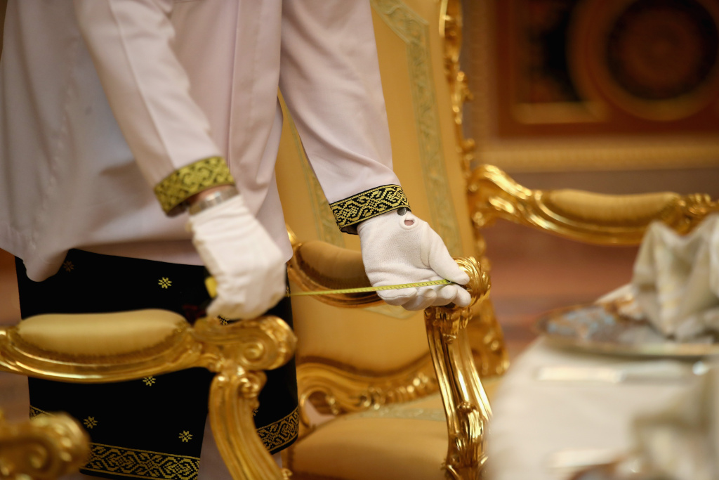 A palace worker measures the distance between chairs with a tape measure ahead of a high tea at the Sultan of Brunei's Palace on November 2, 2017 in , Bandar Seri Begawan, Brunei.