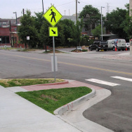 A 'corner bulb out' extends the sidewalk into the street, shortening the distance a pedestrian has to walk, and helping slow auto traffic.