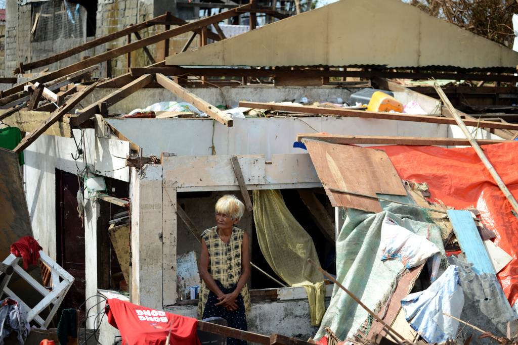 A survivor stands among the debris of a house destroyed by Super Typhoon Haiyan in Tacloban in the eastern Philippine island of Leyte on November 11, 2013.